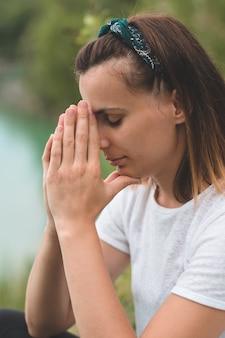 Mulher fechou os olhos, orando ao ar livre. mãos postas em conceito de oração pela fé, espiritualidade e religião