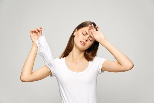 Mulher fechou os olhos segurando a mão na máscara médica na testa.