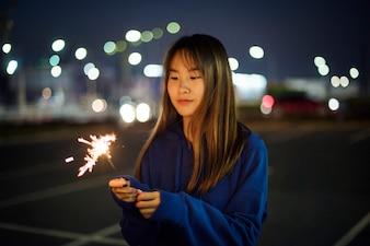 Mulher felicidade e jogando fogo de artifício