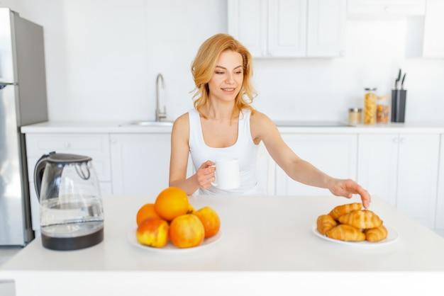 Mulher feliz à mesa, café da manhã de frutas na cozinha.