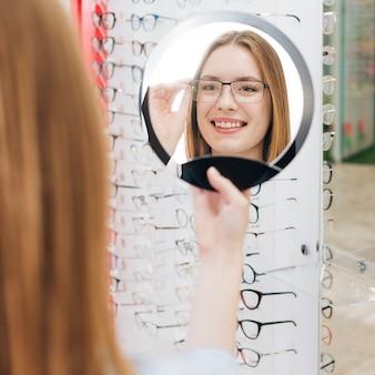 Mulher feliz à procura de novos óculos no optometrista