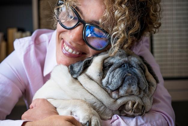 Mulher feliz abraça seu cão pug com amor e amizade. conceito de melhor amigo para sempre e dono do animal aproveitando o tempo em casa Foto Premium