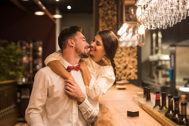 Mulher feliz abraçando homem alegre no balcão de bar