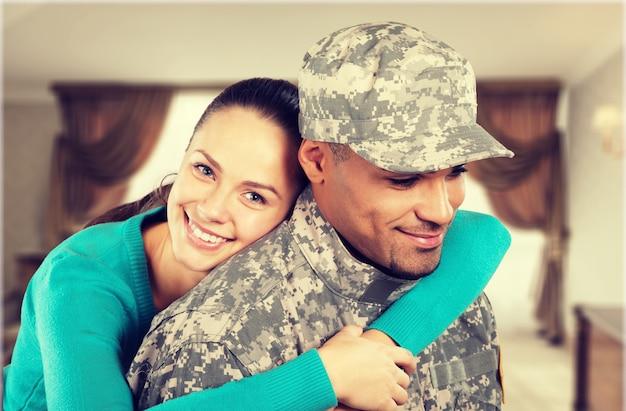 Mulher feliz abraçando militar em casa