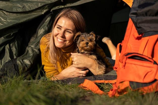 Mulher feliz abraçando o cachorro e sentada na barraca