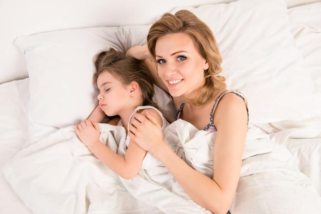 Mulher feliz abraçando seu filho enquanto ela dormia
