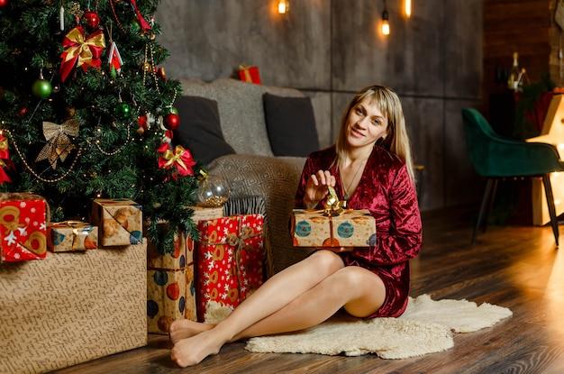 Mulher feliz abrindo a caixa de presente. loira luxuosa em vestido vermelho com presente de natal. feliz natal