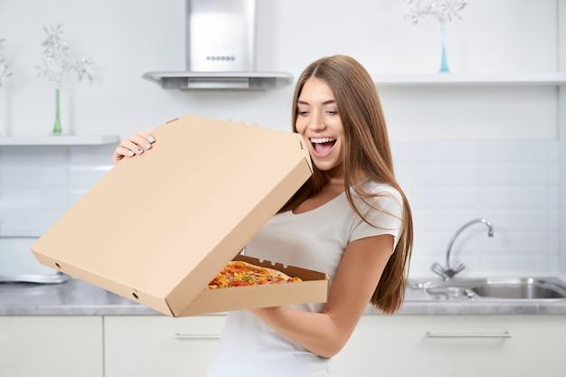 Mulher feliz abrindo caixa de pizza com prazer