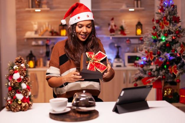 Mulher feliz abrindo uma caixa de presente durante uma videochamada online