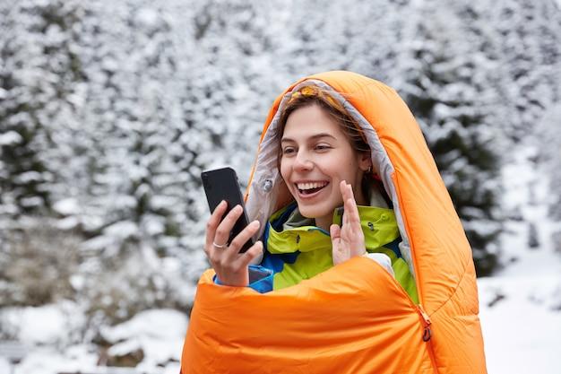 Mulher feliz acena alegremente para a câmera do celular, faz videochamada do topo nas montanhas cobertas de neve