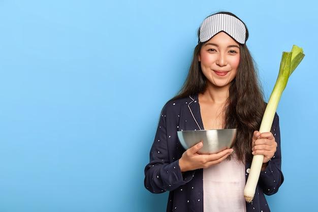 Mulher feliz acorda cedo para preparar o café da manhã, vestida com uma roupa de dormir confortável, segura uma tigela de aço e alho-poró verde