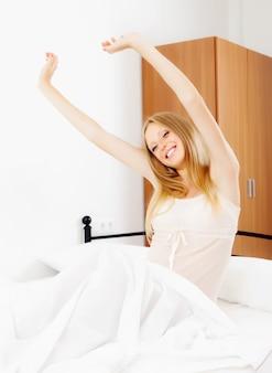 Mulher feliz acordando na folha branca
