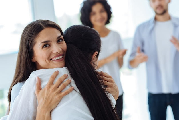 Mulher feliz alegre encantada sorrindo e de ótimo humor enquanto abraça sua amiga