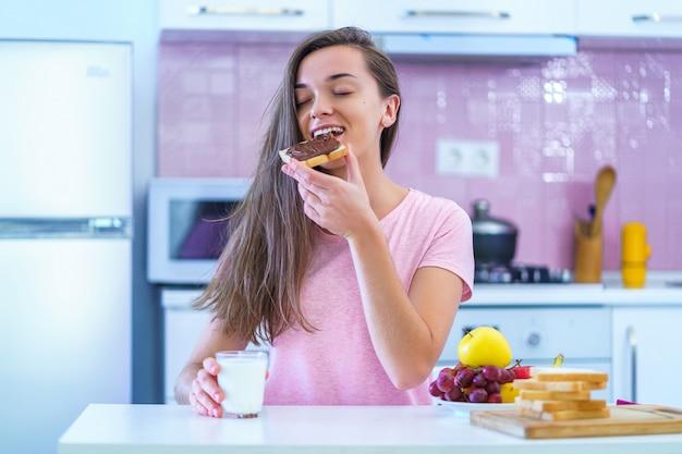 Mulher feliz alegre jovem café da manhã comendo sanduíche com creme de chocolate porca em um café da manhã doce e saudável em casa