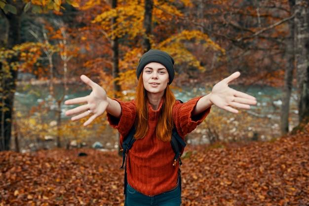 Mulher feliz alpinista na floresta de outono perto do rio gesticulando com as mãos
