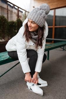 Mulher feliz amarrar cadarços na figura de skate na pista