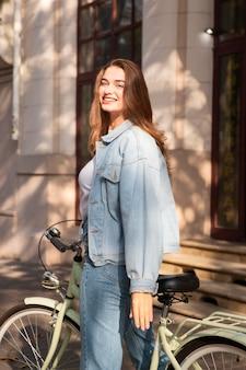 Mulher feliz andando de bicicleta lá fora na cidade