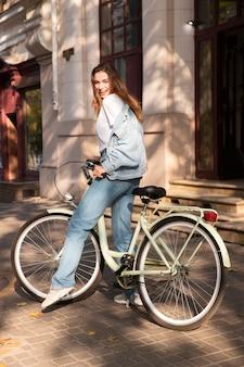 Mulher feliz andando de bicicleta na cidade