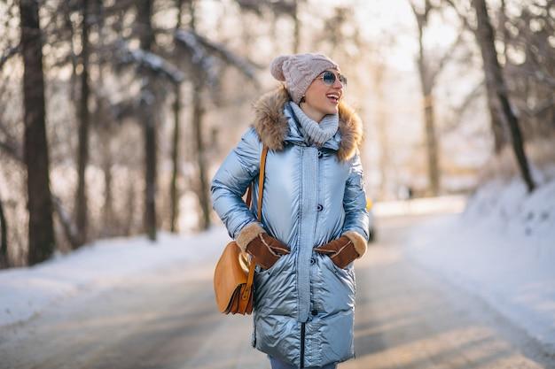 Mulher feliz andando em um parque de inverno
