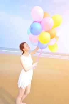 Mulher feliz andando na praia com balões