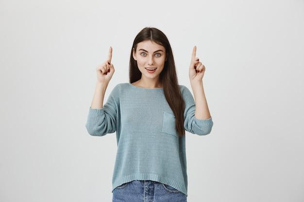 Mulher feliz animada, apontando os dedos para cima, sendo surpreendido