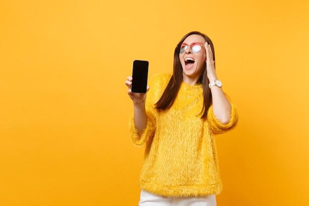 Mulher feliz animada em copos de coração, colocando a mão na cabeça, segurando o telefone móvel com tela vazia preta em branco, isolada no fundo amarelo brilhante. estilo de vida de emoções sinceras de pessoas. área de publicidade.