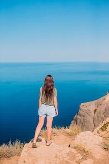 Mulher feliz ao ar livre na beira do penhasco apreciar a vista sobre a rocha no topo da montanha