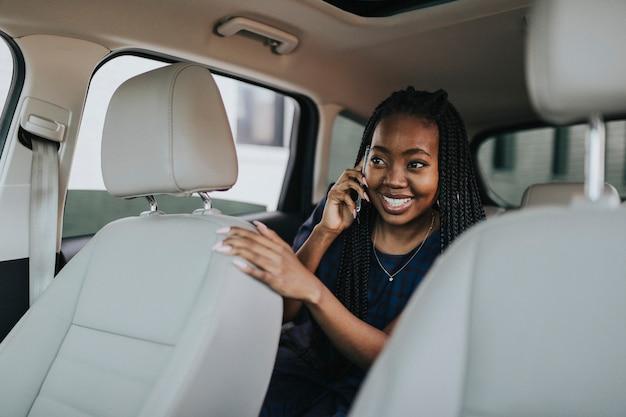 Mulher feliz ao telefone em um carro