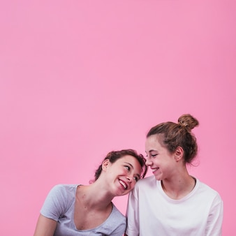 Mulher feliz, apoiando-se no ombro da mulher sobre fundo rosa