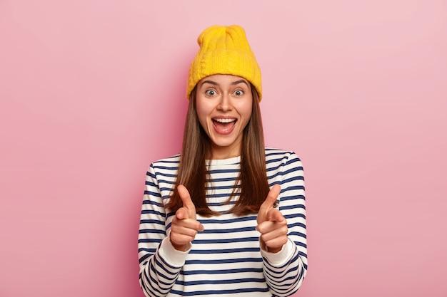 Mulher feliz aponta diretamente para a câmera, expressa sua escolha com um gesto de arma de dedo, usa um chapéu amarelo e um macacão casual listrado,