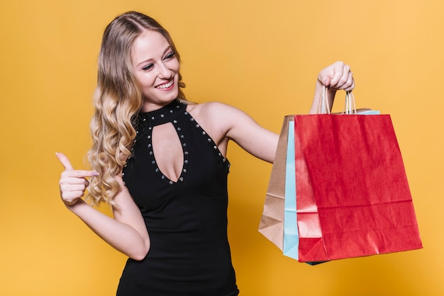 Mulher feliz, apontando para sacos de papel