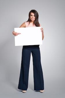 Mulher feliz apontando para um quadro branco vazio
