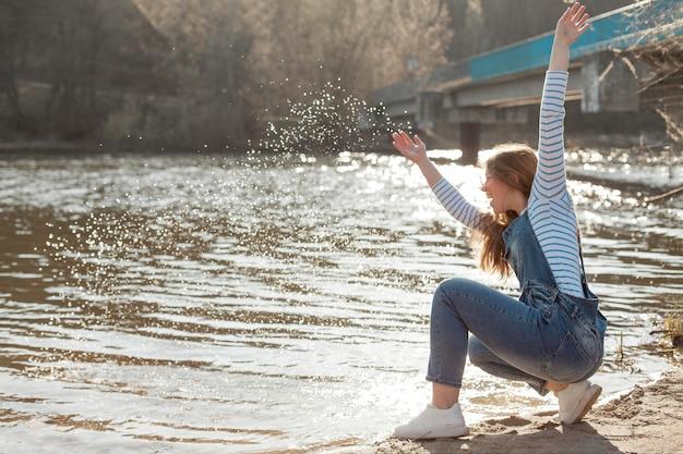 Mulher feliz, aproveitando seu tempo à beira do lago