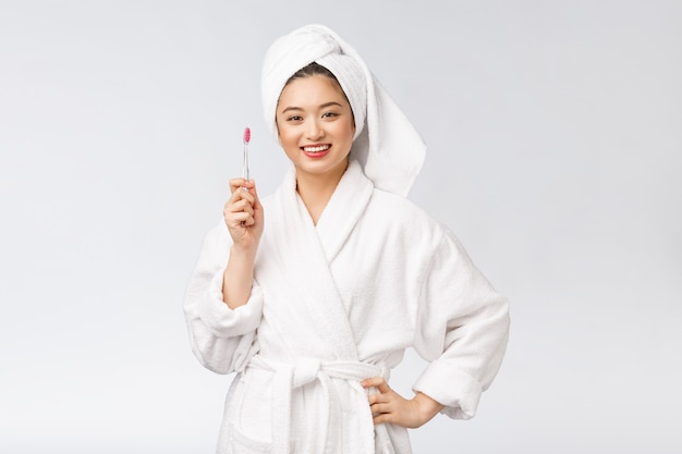 Mulher feliz asiática com escova de dentes no humor de manhã roupão.