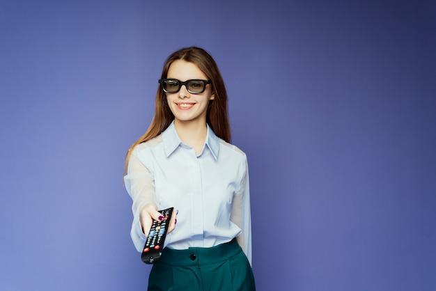 Mulher feliz assistindo filmes e programas de tv na tv inteligente com óculos 3d. a menina bonita em um fundo lilás muda de canal usando um controle remoto