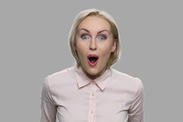 Mulher feliz atordoada em fundo cinza. jovem mulher animada close-up. expressões faciais e emoções humanas.