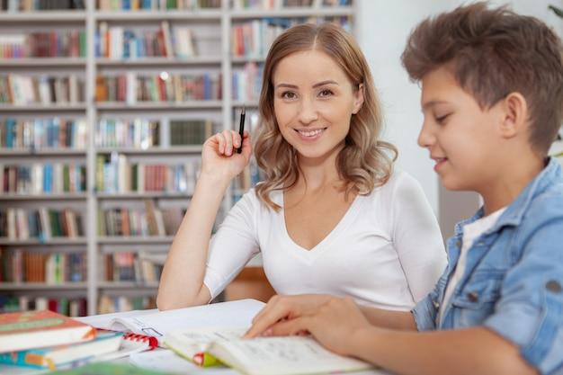 Mulher feliz atraente sorrindo enquanto seu filho está lendo um livro na biblioteca