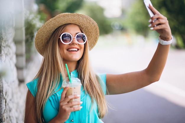 Mulher feliz bebendo café e fazendo selfie