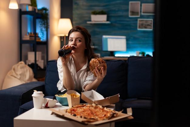 Mulher feliz bebendo cerveja, comendo hambúrguer saboroso e delicioso assistindo filme da série de documentários