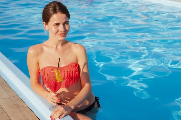 Mulher feliz bonita que aprecia o cocktail saboroso na piscina, espaço da cópia. encantadora turista feminina desfrutando de sua estadia no resort de luxo
