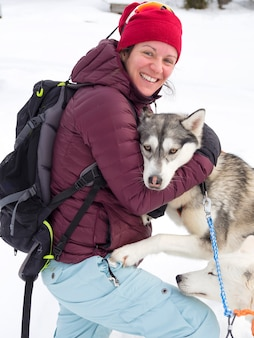 Mulher feliz brincando com cachorro de trenó na neve