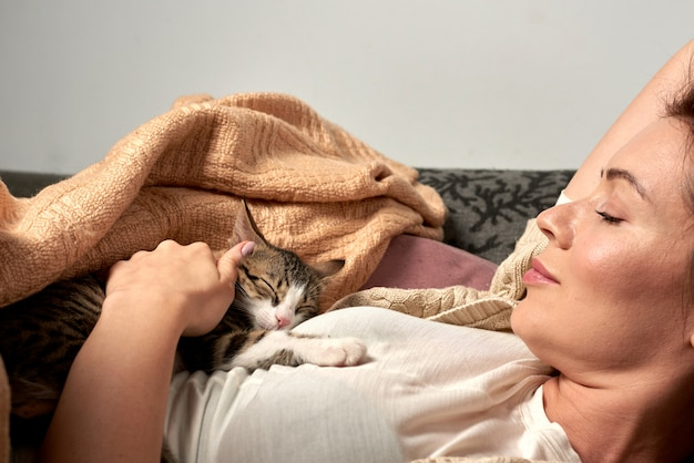 Mulher feliz brincando com o gato no quarto