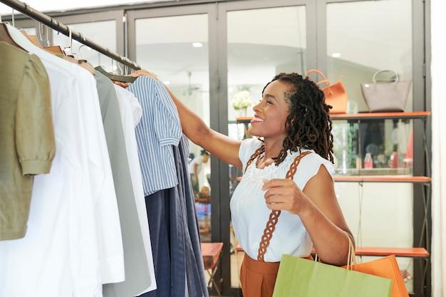 Mulher feliz buyng roupas novas