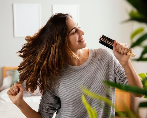 Mulher feliz cantando para a escova de cabelo em casa
