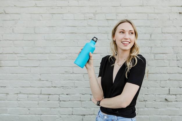 Mulher feliz carregando uma garrafa térmica