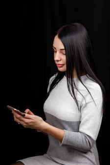 Mulher feliz caucasiana de beleza olhando para o telefone e escrevendo uma mensagem no espaço negro.