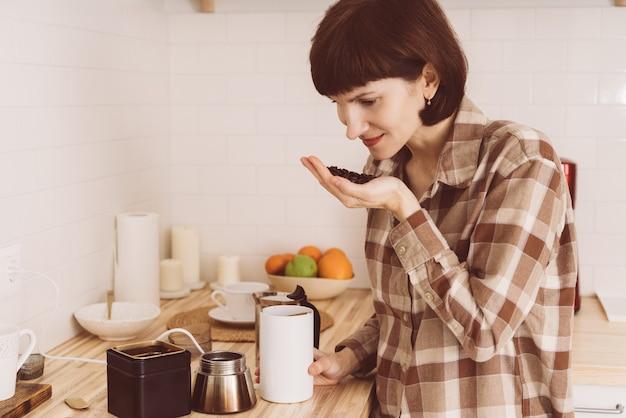 Mulher feliz cheirando café em lata e cheirando o aroma. fêmea a inalar feijão fresco