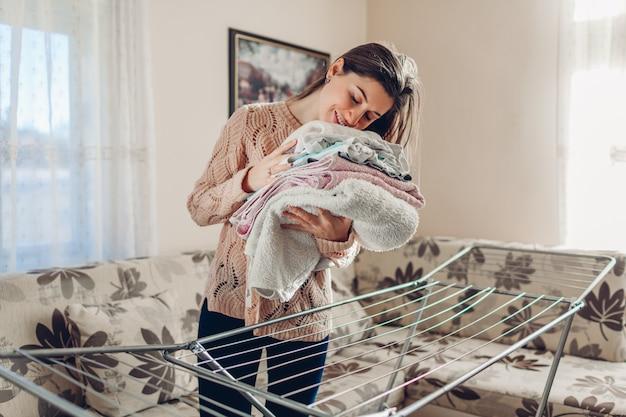 Mulher feliz cheirando reuniu roupas limpas do secador na pilha