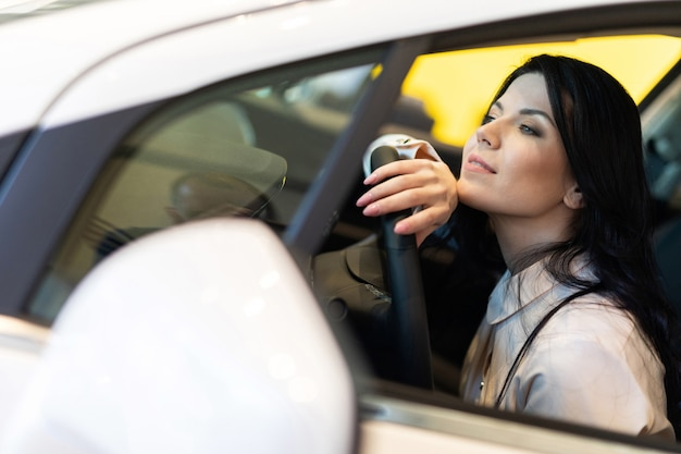 Mulher feliz cliente comprando um carro novo no centro de negociação