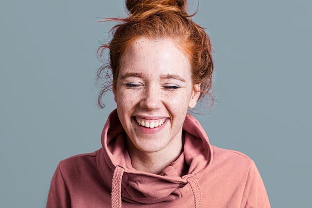 Mulher feliz close-up com capuz rosa e fundo cinza